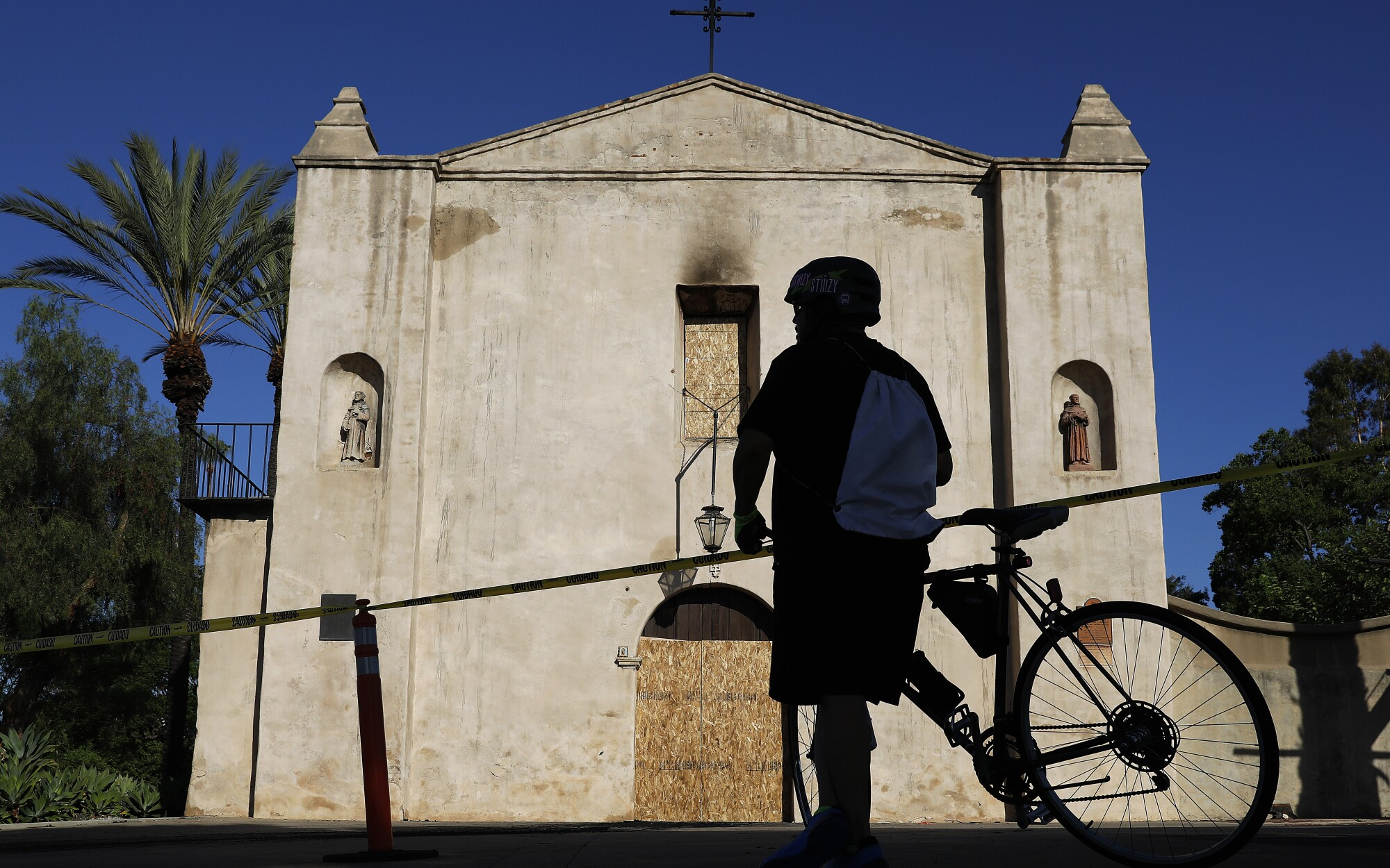 """A bicyclist stops Sunday in front of the 215-year-old San Gabriel Mission. A fire early Saturday caused """"extensive damage."""""""