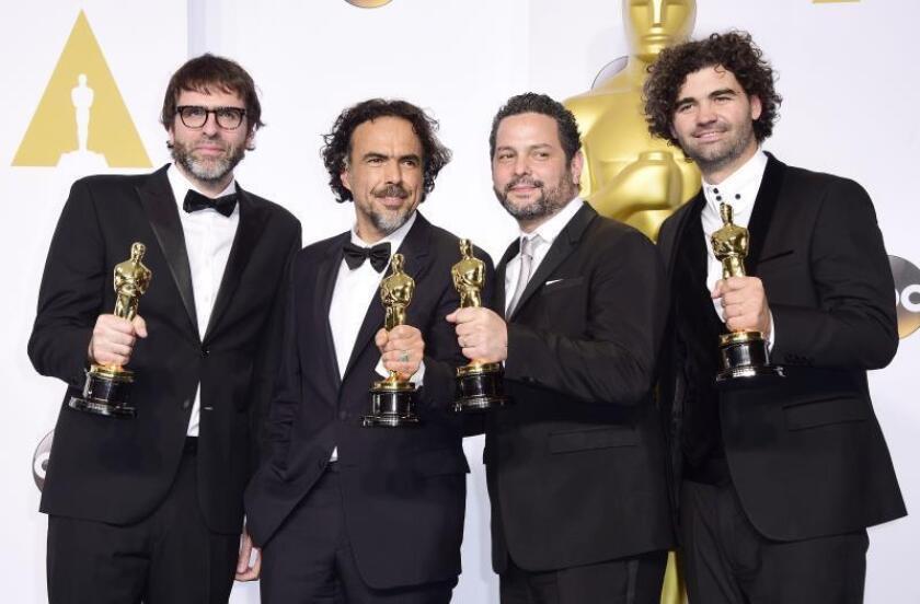 Nicolas Giacobon (i) con Alejandro G. Inarritu (2i) con sus Oscar en la edición de 2015 de estos premios. EFE/Archivo