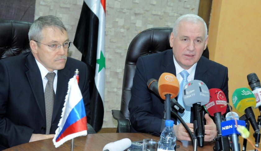 Russian Ambassador Azmatullah Kulmohammadov, left, and Syrian Oil Minister Suleiman Abbas during an oil-agreement signing ceremony Wednesday in Damascus, Syria.