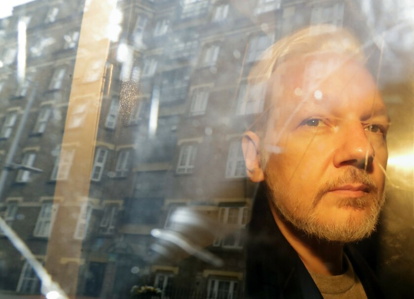 """FILE - In this Wednesday May 1, 2019 file photo buildings are reflected in the window as WikiLeaks founder Julian Assange is taken from court, where he appeared on charges of jumping British bail seven years ago, in London. Assange relayed how he """"binge-watched"""" the suicide of the former Bosnian Croat general in a U.N. courtroom three years ago, a doctor who visited the WikiLeaks founder on several occasions while he was in the Ecuadorian Embassy in London told an extradition hearing Thursday, Sept. 24, 2020. (AP Photo/Matt Dunham, File)"""