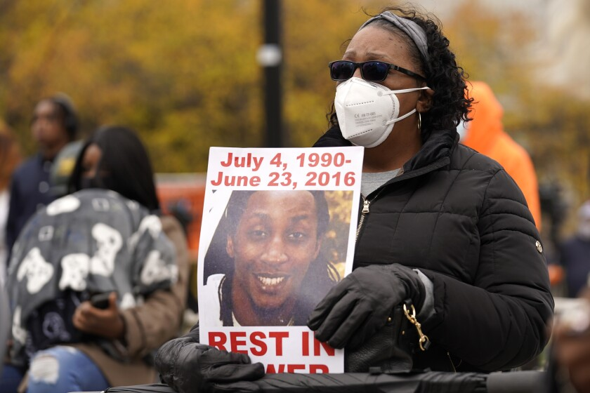 FILE - In this Oct. 29, 2020 file photo, Jay Anderson's mother, Linda Anderson, holds a sign during a Get Out The Vote rally in Chicago. An attorney representing the families of three people who died at the hands of a former Wisconsin police officer filed another federal lawsuit against him Wednesday, Oct. 13, 2021, saying his department taught him to view Black people as dangerous. The lawsuit alleges that former Wauwatosa Police Officer Joseph Mensah violated Jay Anderson's constitutional rights when he shot and killed Anderson after discovering him sleeping in a park after hours in 2016. (AP Photo/Nam Y. Huh File)