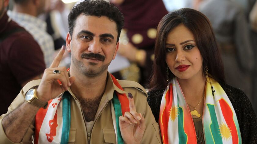 Iraqi Kurds show their ink-stained fingers after casting their votes in the Kurdish independence ref