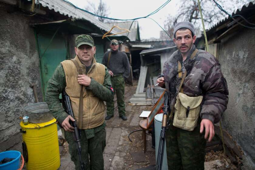 Pro-Russian gunmen stand outside their house in Donetsk, Ukraine, on Thursday. Despite a two-month-long truce, fighting continued at the city's airport, which is held by government troops.