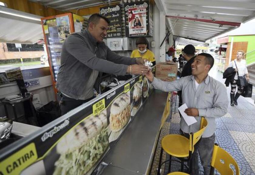"""En esta imagen del 11 de junio de 2019, Gerson Briceño, propietario del restaurante de comida rápida """"Arepas Cafe"""", sirve a un cliente en Bogotá, Colombia, el martes 11 de junio de 2019. (AP Foto/Fernando Vergara)"""
