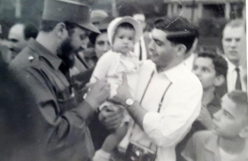 """Fotografía cedida de Fidel Castro firmando autógrafos al lado de una bebé estadounidense durante la semana de primavera de 1959, en la que el líder revolucionario cubano pisó Washington (EE.UU.) por primera vez. En la misma se puede leer, escrita en inglés, una dedicatoria firmada por Fidel que reza """"Para la graciosa pequeña que conocí en Washington y a la que quiero"""", para Sherry Hayes Santana, entonces una bebé de 16 meses, cuyos padres se toparon con el entonces """"Barbudo"""" cubano de 32 años cerca de la antigua sede diplomática cubana de la calle 16. La legendaria longevidad de Fidel Castro fue tan tozuda que ya es casi imposible encontrar testigos de la semana de primavera de 1959 en el que el líder revolucionario cubano, cuyas cenizas van camino a su sepultura, pisó Washington por p"""