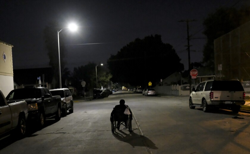 A woman pushes her wheelchair at night near South Hoover Street and West Florence Avenue in South Los Angeles. She was counted by volunteers in homeless count in South L.A.