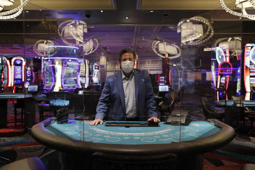 Bill Hornbuckle of MGM Resorts International stands behind a see-through barrier at a blackjack table in the Bellagio casino.