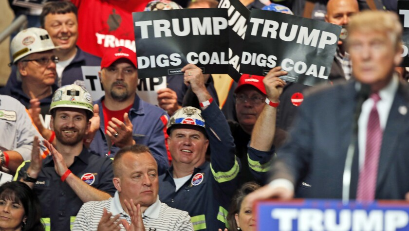 Coal miners wave signs as then-candidate Donald Trump speaks at a rally in Charleston, W.Va., in May 2016.