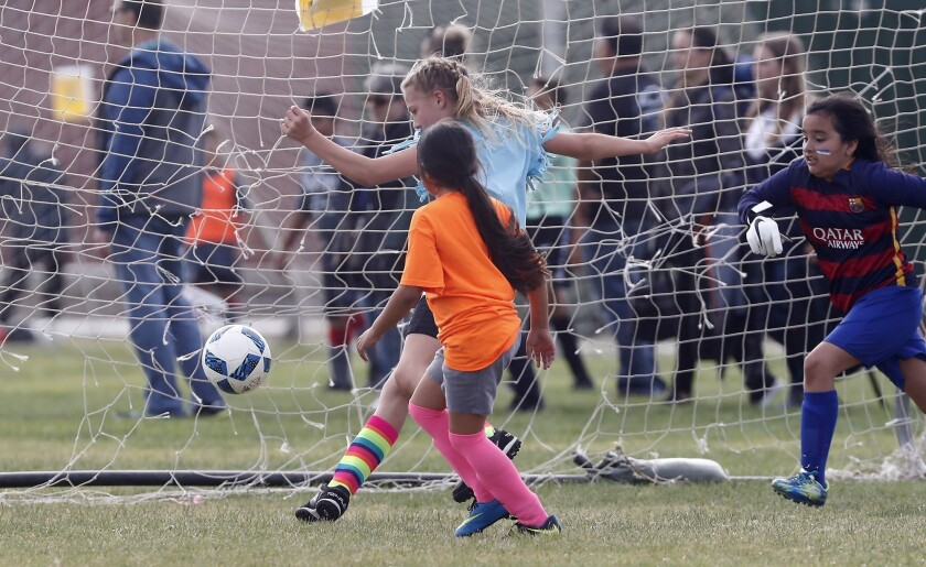 Costa Mesa St. Joachim Catholic School's Ava Farrow, center, scores against Costa Mesa Wilson's Emma