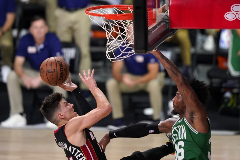 Miami Heat guard Tyler Herro takes a shot as Boston Celtics' Marcus Smart defends.