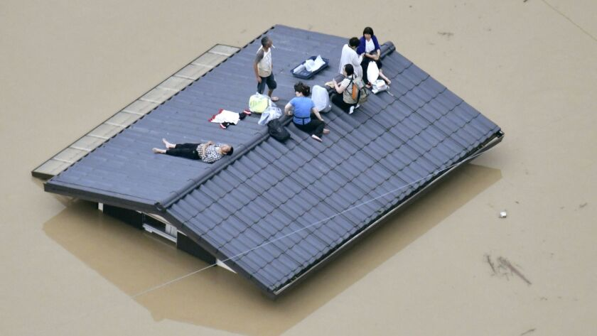 People waif to be rescued on the top of a house almost submerged in floodwaters caused by heavy rain