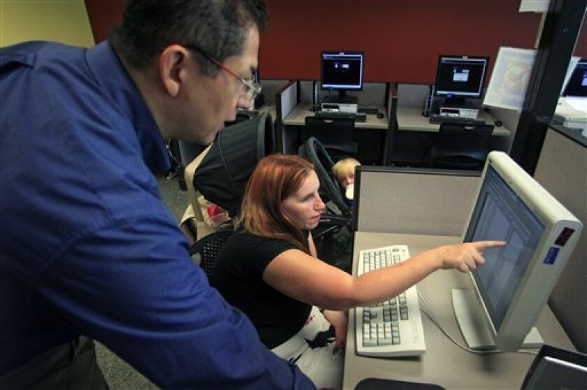 FILE-In this Sept. 21, 2012, file photo, Deanna Aguilera, 30, of Salt Lake City, right, receives assistance from employment counselor Frank Trivino while job searching at Workforce Services, in Salt Lake City. The number of Americans seeking unemployment benefits plunged 26,000 last week to a seasonally adjusted 359,000, a hopeful sign for the job market. The Labor Department said Thursday that the four-week average, a less volatile measure, declined 4,500 to 374,000. That's the first drop in six weeks. (AP Photo/Rick Bowmer, File)