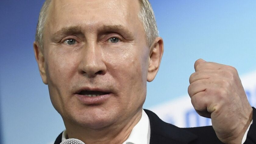 Russian President and Presidential candidate Vladimir Putin gestures as he speaks at his campaign he