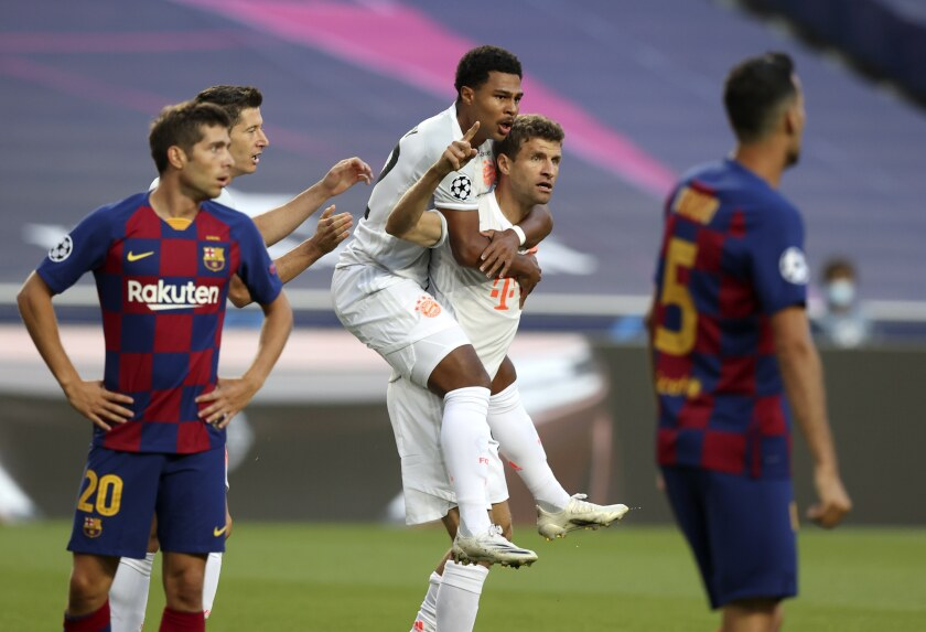 Bayern's Thomas Mueller, bottom center, celebrates after scoring the opening goal during the Champions League quarterfinal soccer match between Barcelona and Bayern Munich in Lisbon, Portugal, Friday, Aug. 14, 2020. (Rafael Marchante/Pool via AP)