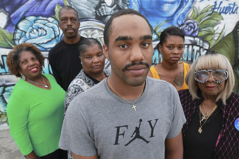 Miguel Lucas, center, who was bitten in the face by a cellmate while incarcerated in San County jail, with the family of Reginald Harmon Jr., the man who assaulted him, from left, aunt Donnetta Moore, father Reggie Harmon Sr., mother Alicia Muhammad, sister Samatha Harmon, and grandmother Kathleen Harmon, in Encanto on Wednesday, October 16, 2019.