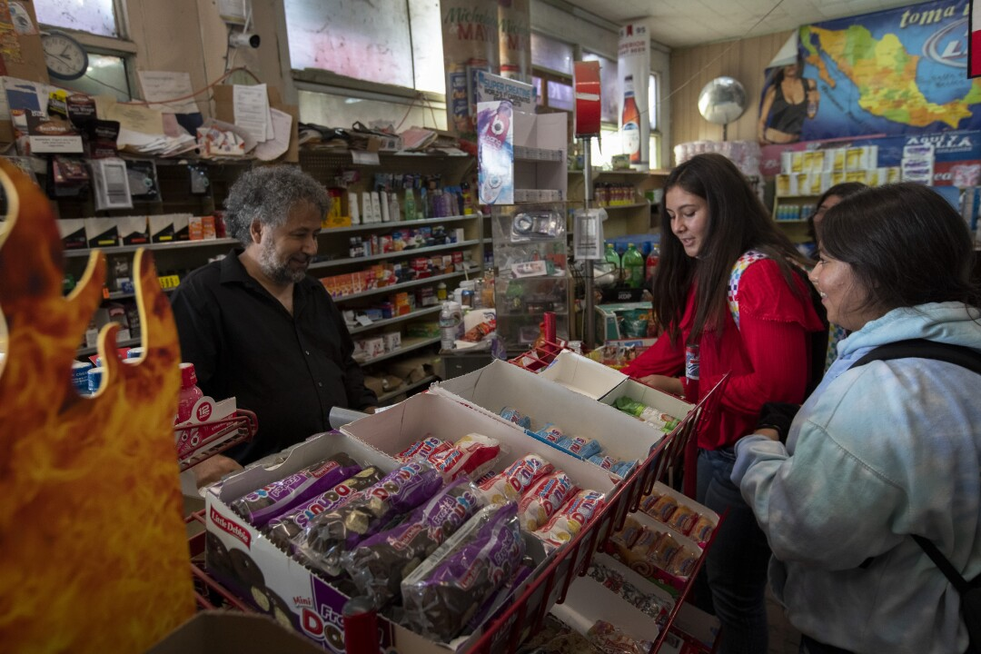 High school girls just off a bus crowd the counter at Stratford Market as owner Mahmod Alrihimi, left, rings up purchases.