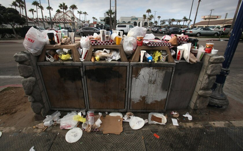 Trash, including plenty of plastic bags, overflows from bins at Belmont Park in Mission Beach on July 5.