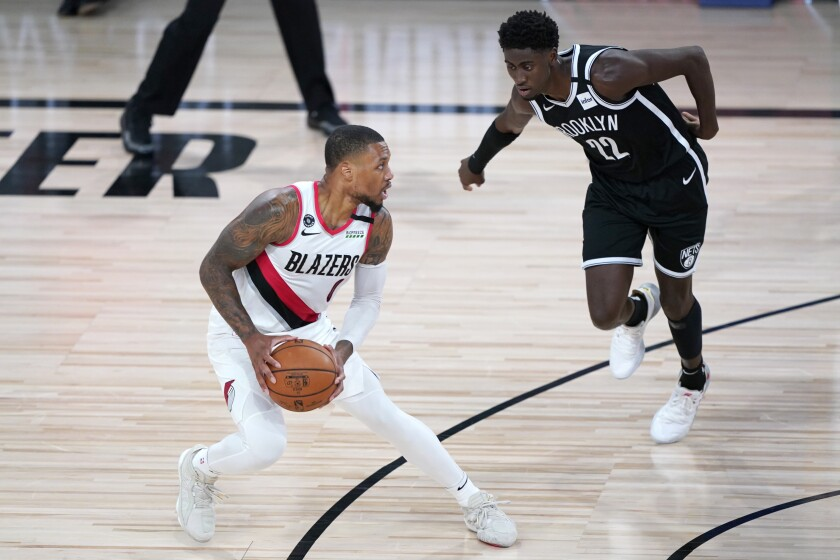 Portland Trail Blazers' Damian Lillard, left, works the floor against Brooklyn Nets' Caris LeVert during the first half of an NBA basketball game Thursday, Aug. 13, 2020 in Lake Buena Vista, Fla. (AP Photo/Ashley Landis, Pool)