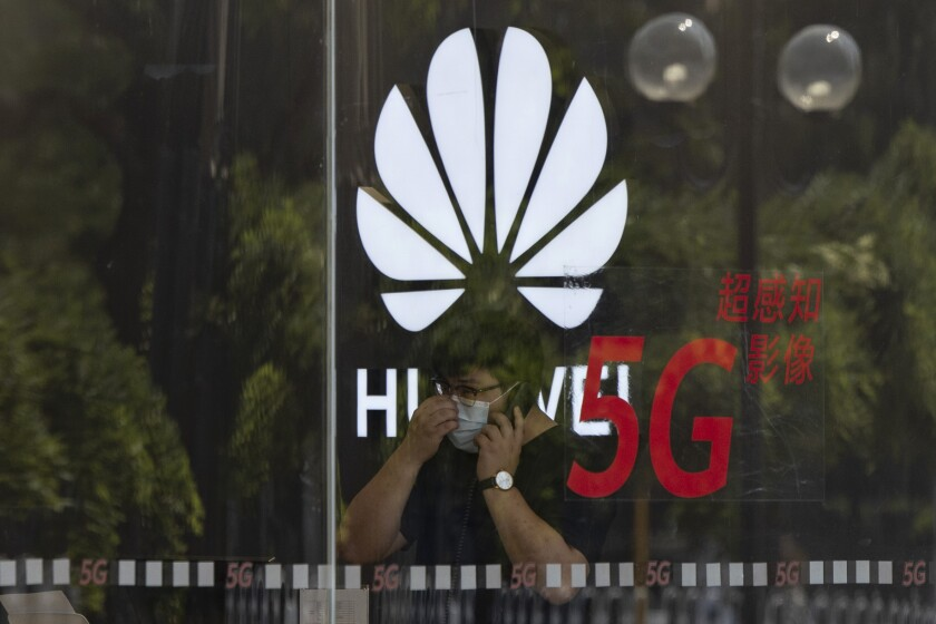 A worker speaks on the phone near the Huawei logo in a store