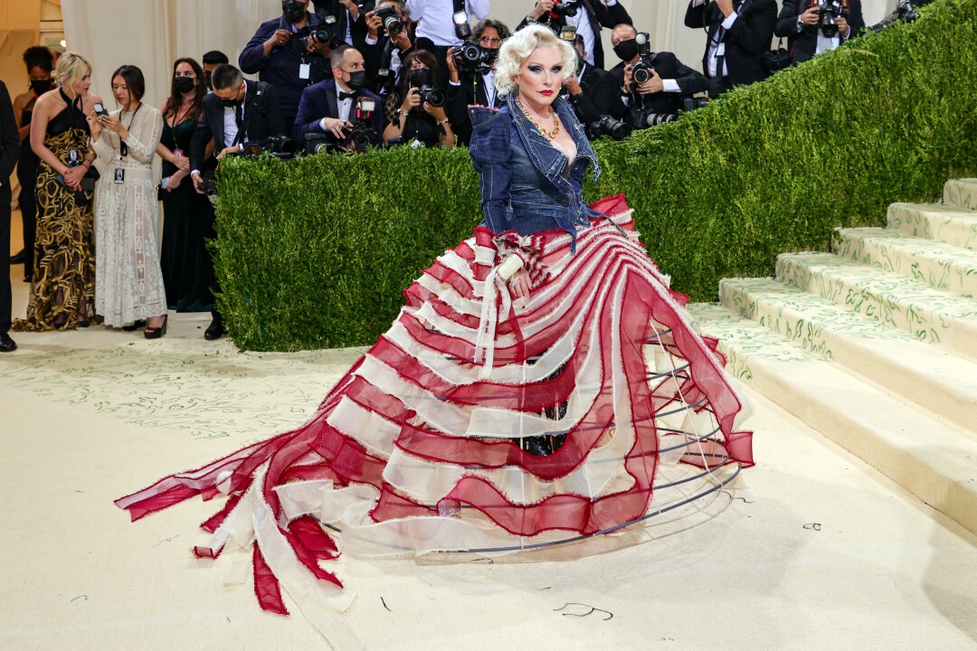 A woman in a flag-stripe gown and blue denim jacket.