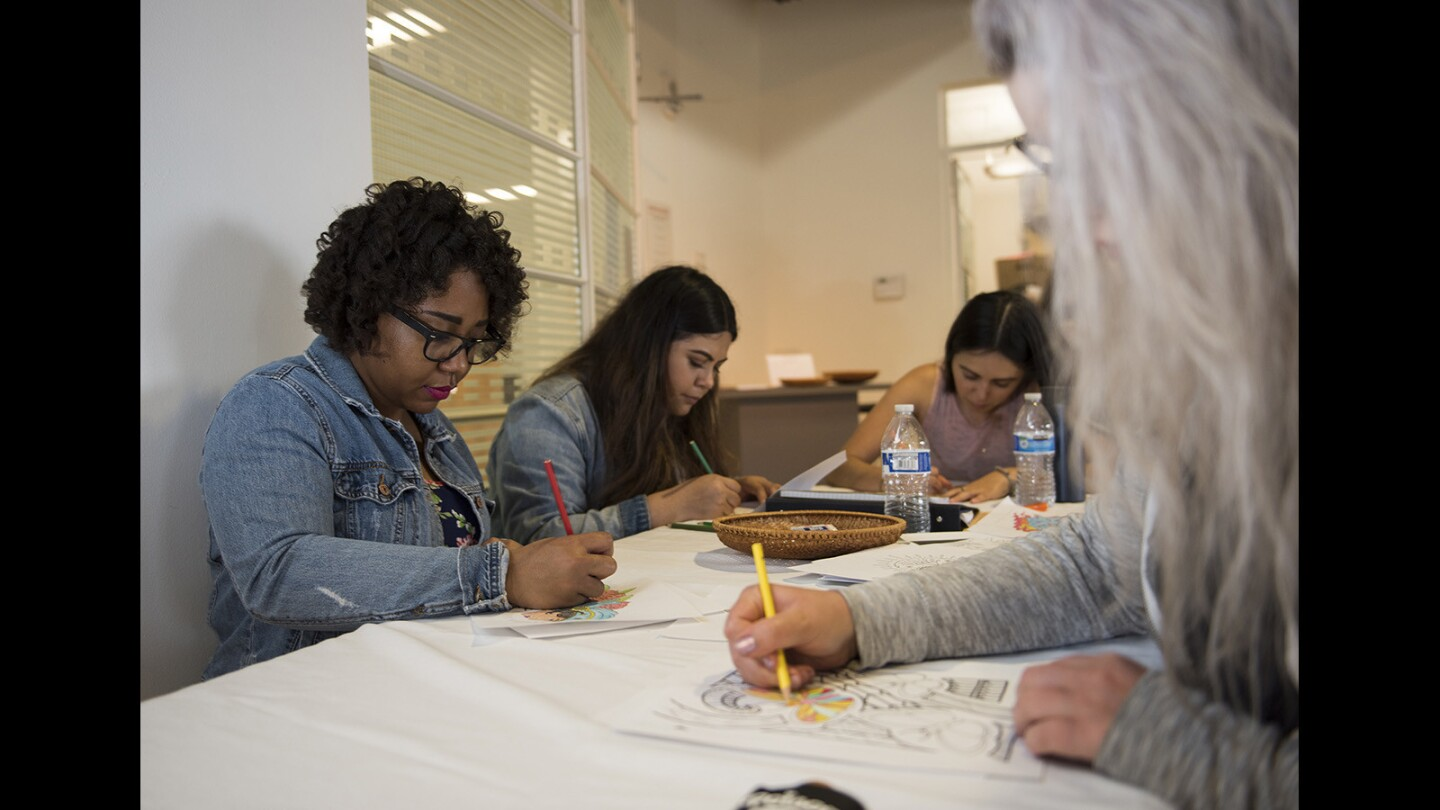 """From left, Candice Daniel, Citlalli Hidrogo, Victoria Ramirez and Haley Ruiz color tattoo outlines on March 17. The Cal State Fullerton students helped install the """"Tattooed & Tenacious: Inked Women in California's History"""" exhibit as part of the anthropology museum practicum class at Cal State Fullerton."""