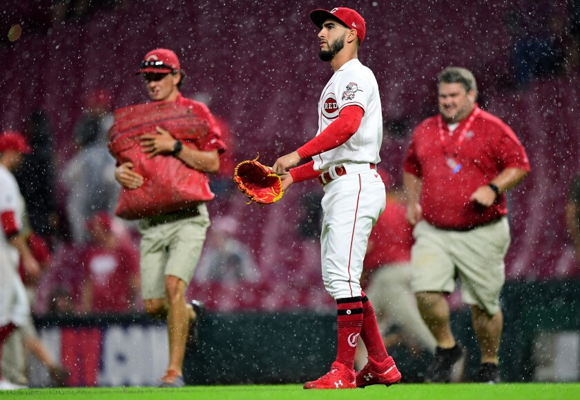 Reds pitcher Cionel Perez walks off as grounds crew members rush onto the field