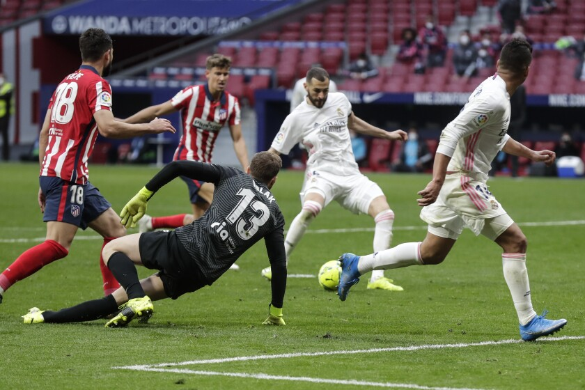 Real Madrid's Karim Benzema scores his side's opening goal during the Spanish La Liga soccer match between Atletico Madrid and Real Madrid at the Wanda Metropolitano stadium in Madrid, Spain, Sunday, March 7, 2021. (AP Photo/Manu Fernandez)
