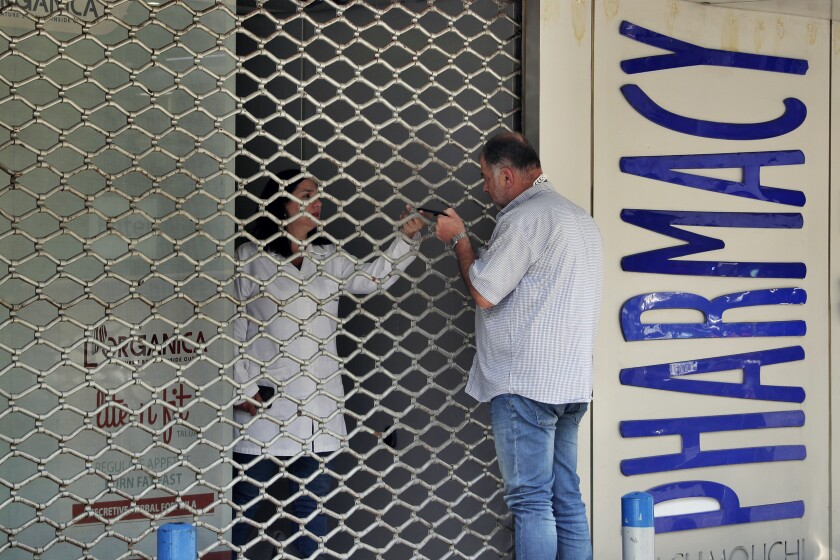 A man speaks with a pharmacist through a closed door of a pharmacy, in Beirut, Lebanon, Friday, June 11, 2021. Pharmacies across Lebanon began a two-day strike Friday, protesting severe shortages in medicinal supplies that is increasingly putting them in confrontation with customers and patients searching for medicines. The shortages are affecting everything from medicines for chronic illnesses to pain relievers to infant milk. (AP Photo/Bilal Hussein)