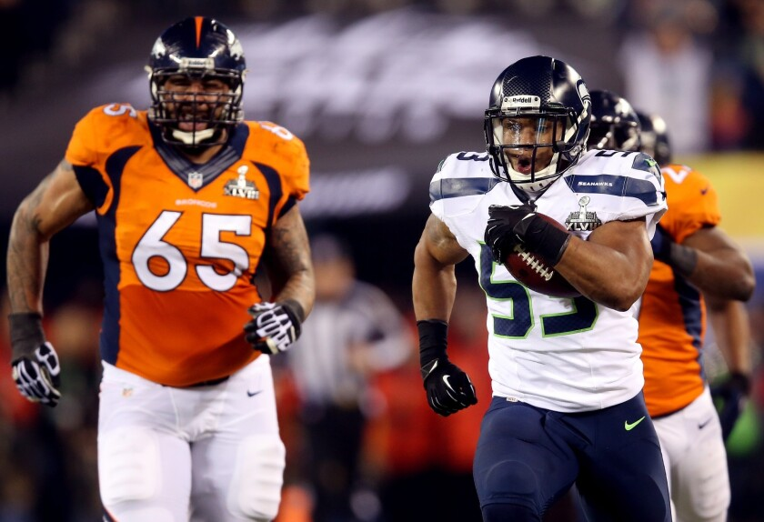 Seattle linebacker Malcolm Smith leaves Denver lineman Louis Vasquez (65) in his wake on a 69-yard interception return for a touchdown in the second quarter.