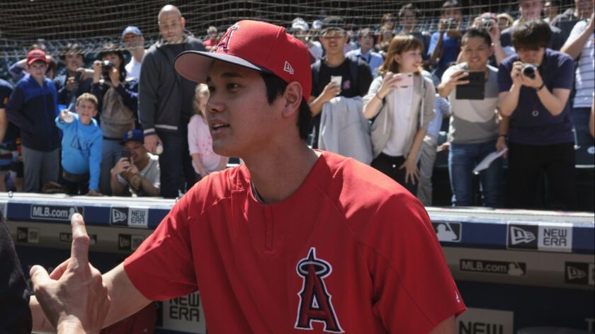 Los Angeles Angels' Shohei Ohtani greets fans on field with others taking photographs behind during