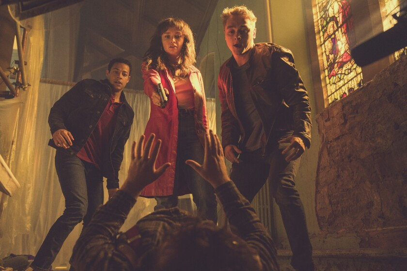 Olivia Cooke, Daryl McCormack and Ben Hardy stand over a man lying on the floor