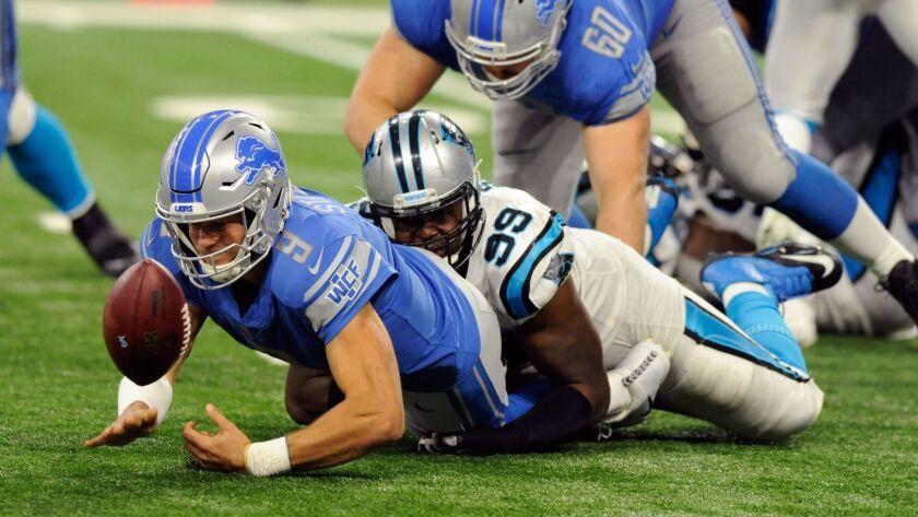 Lions quarterback Matthew Stafford fumbles the ball after a tackle by Carolina Panthers defensive tackle Kawann Short.