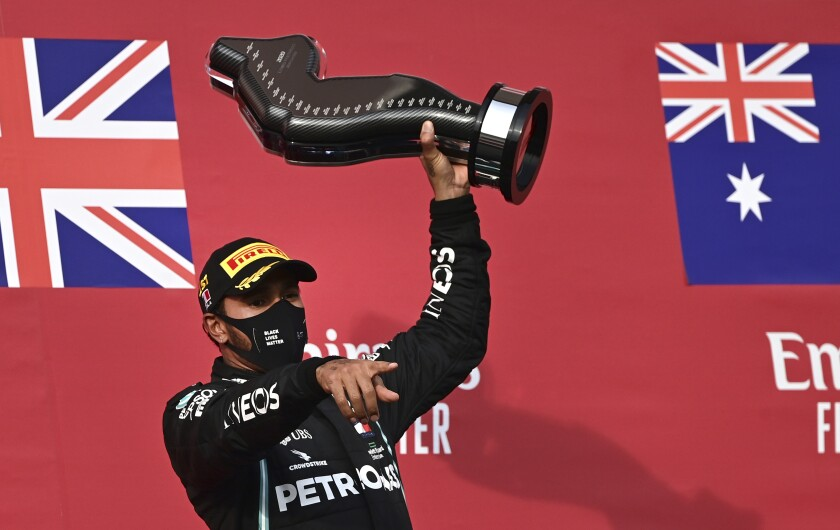 Lewis Hamilton holds up the trophy on the podium after winning the Emilia Romagna Formula One Grand Prix.