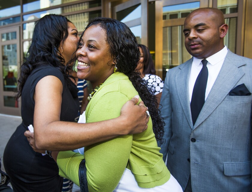Shanesha Taylor is congratulated as Rev. Jarrett Maupin looks on outside Maricopa County Superior Court in Phoenix. Prosecutors and Taylor reached a deal to allow her to avoid prosecution for leaving her two young sons alone in a hot car while she was at a job interview.