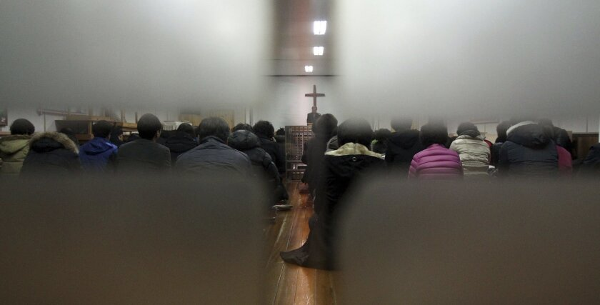 Members from Jincheon Jungang Presbyterian Church attend a service at their church in Jincheon, South Korea, Monday, Feb. 17, 2014. A bombing that killed three South Koreans and an Egyptian driver on the Sinai Peninsula targeted a bus filled with Korean members from the church who had saved for years to visit sites mentioned in the Bible on their church's 60th anniversary, officials said Monday. (AP Photo/Yonhap, Kim Hyung-woo) KOREA OUT