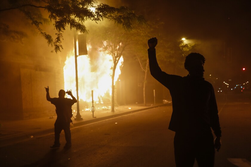 Protesters react along Chicago Avenue as fires rage along a strip of businesses, early Saturday, May 30, 2020, in Minneapolis. Protests continued following the death of George Floyd, who died after being restrained by Minneapolis police officers on Memorial Day. (AP Photo/John Minchillo)
