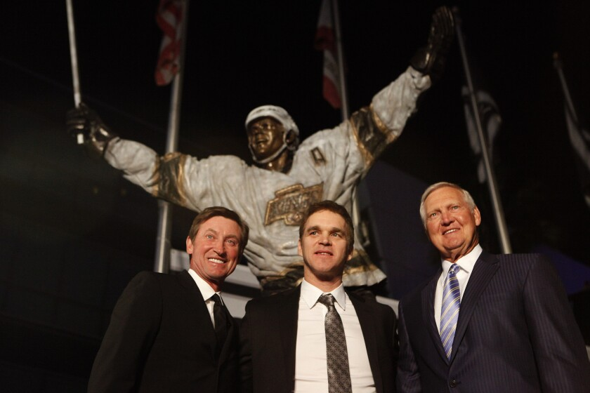 Kings hockey greats Wayne Gretzky, left, and Luc Robitaille, center, stand with Lakers legend Jerry West, right, in front of Robitaille's new bronze statue that was unveiled outside Staples Center.