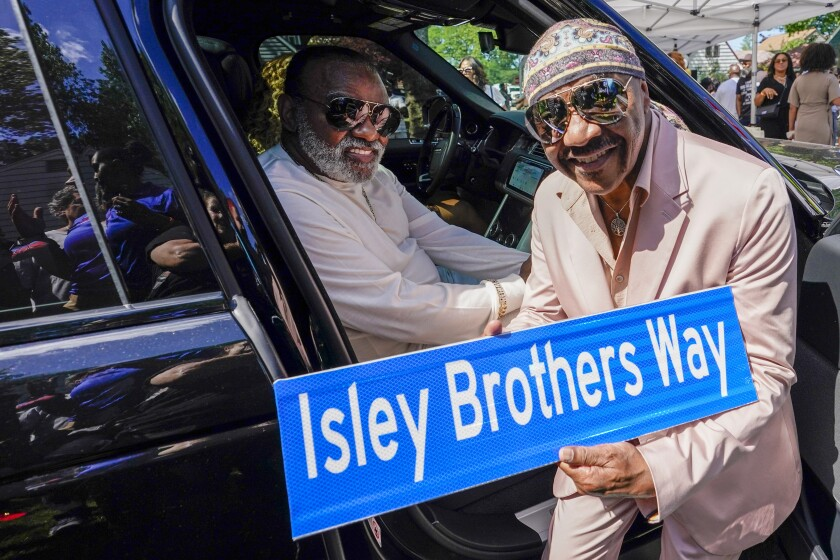 """Ron Isley, left, and Ernie Isley pose for a photo with the street sign dedicated to them during a street renaming ceremony, Thursday, June 24, 2021, in Teaneck, N.J. Two New Jersey towns have renamed streets in honor of the Isley Brothers, the legendary R&B group behind songs such as, """"Shout,"""" """"Twist and Shout"""" and """"It's Your Thing."""" Ron Isley and Ernie Isley attended separate ceremonies Thursday in Teaneck and Englewood, neighboring towns outside New York City where they lived during the band's heyday in the 1960s. (AP Photo/Mary Altaffer)"""