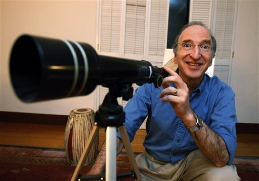 Nobel Prizes winner for physics Saul Perlmutter smiles as he poses with his daughter's telescope at his home in Berkeley, Calif., Tuesday, Oct. 4, 2011 after hearing he had won. The Royal Swedish Academy of Sciences said American Perlmutter would share the 10 million kronor ($1.5 million) award with U.S.-Australian Brian Schmidt and U.S. scientist Adam Riess. Working in two separate research teams during the 1990s, Perlmutter in one and Schmidt and Riess in the other, the scientists raced to map the universe's expansion by analyzing a particular type of supernovas, or exploding stars. (AP Photo/Paul Sakuma)