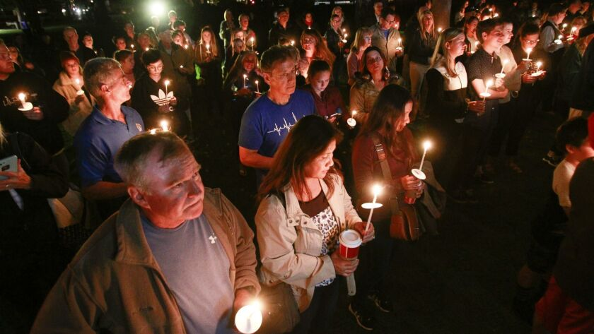 CORONADO, November 8, 2018   People hold candles for Justin Meek, 23, who is one of the twelve peopl