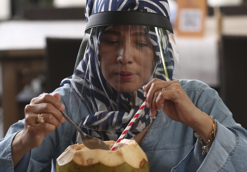 A woman wearing protective face shield as a precaution against the new coronavirus enjoys a fresh coconut at a seafood restaurant on the outskirts of Jakarta, Indonesia, Wednesday, June 10, 2020. As Indonesia's overall virus caseload continues to rise, Jakarta has moved to restore normalcy by lifting some restrictions this week, saying that the spread of the virus in the city of 11 million has slowed after peaking in mid-April. (AP Photo/Tatan Syuflana)
