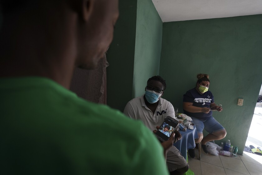 Mensah Montant, center, and his wife Virginia Salazar visit with a Haitian migrant at an apartment in Ciudad Acuna, Friday, Sept. 24, 2021. Montant knows how it feels to be a stranger in a strange land: He arrived in Mexico as an immigrant himself nine years ago, and now works as a tailor. (AP Photo/Fernando Llano)