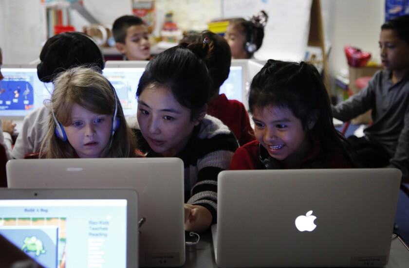 Teacher Michelle Lee, center, works with Audrey Eckert, 6, left, and Jaqueline Hernandez, 5, at Metro Charter Elementary in downtown Los Angeles in June.