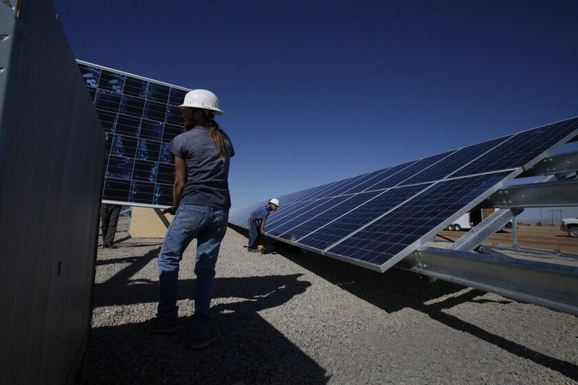 Laborers mount solar panels in the Southern California desert.