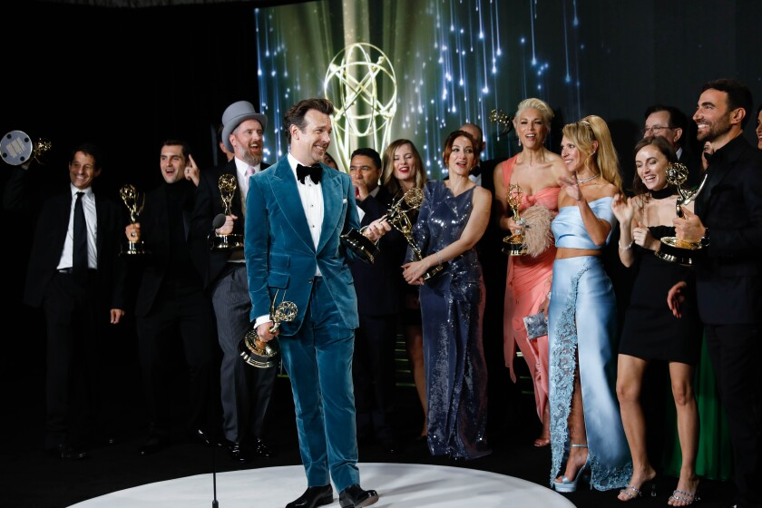 """Jason Sudeikis, in a blue velvet suit, with the """"Ted Lasso"""" team at the Emmy Awards."""
