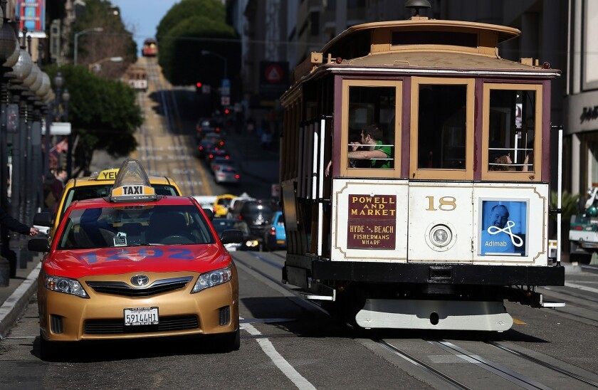 A cable car passes a line of taxicabs in San Francisco. The San Francisco Cab Driver Assn. says that nearly one-third of the city's licensed taxi drivers have started to drive for ride-sharing services such as Lyft, Uber and Sidecar.