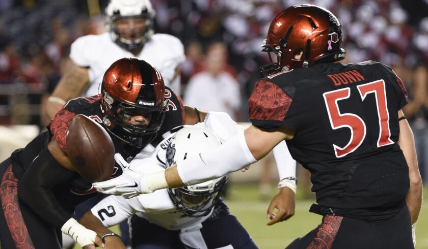 Utah State quarterback Kent Myers (2) fumbles the ball as he's hit by San Diego State defensive lineman Alex Barrett (58), left, and San Diego State linebacker Ryan Dunn (57) during the first half of an NCAA college football game Friday, Oct. 23, 2015 in San Diego. San Diego State recovered the fumble. (AP Photo/Denis Poroy)