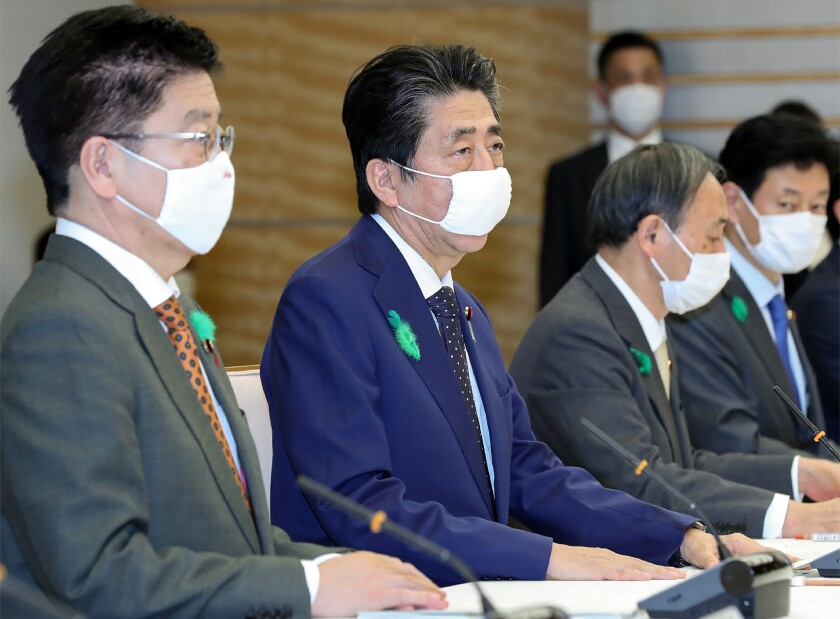 Japanese Prime Minister Shinzo Abe, second from the left, attends a meeting of a coronavirus task force in Tokyo on Thursday.