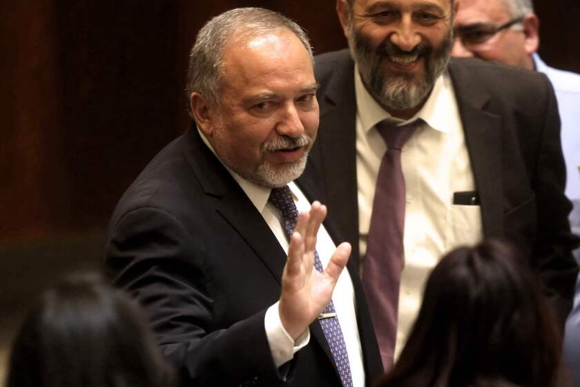 Newly appointed Israeli Defense Minister Avigdor Lieberman waves during a Knesset, or parliament, session in which he was sworn in on May 30, 2016, in Jerusalem.