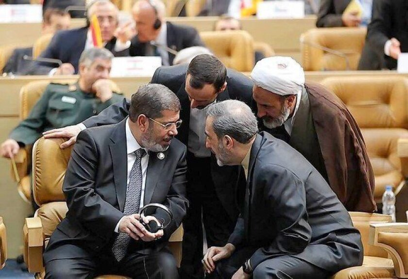 "Egyptian President Mohamed Morsi, left, is surrounded by Iranian officials at the Nonaligned Movement summit in Tehran. ""The blood of the Syrian people is on our necks, and it will not stop unless there is an intervention by all of us,"" he said in a speech."
